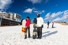Pares jovenes en trajes de esquí, cascos y gafas del esquí que se colocan con Fotos de archivo libres de regalías