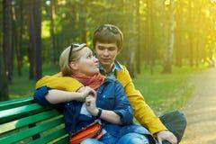Pares jovenes en un banco de parque Imagen de archivo libre de regalías