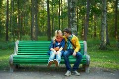 Pares jovenes en un banco de parque Imagenes de archivo
