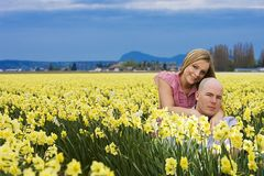 Pares jovenes en un campo de flores Fotografía de archivo libre de regalías