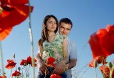 Pares jovenes en un campo rojo de las amapolas Foto de archivo libre de regalías