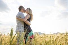 Pares jovenes en un lugar romántico Pares en amor al aire libre en un abarcamiento del campo de trigo Fotografía de archivo libre de regalías