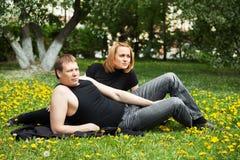 Pares jovenes en un parque de la ciudad Imagen de archivo libre de regalías