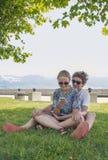 Pares jovenes en un parque de la ciudad Foto de archivo libre de regalías