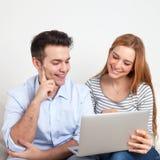 Pares jovenes en un sofá que mira en un cuaderno Imagen de archivo libre de regalías