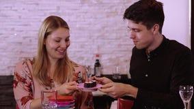 Pares jovenes en un sushi reataurant - consumición del sushi recién hecho de la comida fría almacen de video