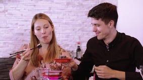 Pares jovenes en un sushi reataurant - consumición del sushi recién hecho de la comida fría metrajes