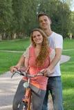 Pares jovenes en una bici Imágenes de archivo libres de regalías