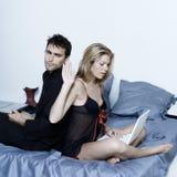 Pares jovenes en una cama Foto de archivo libre de regalías