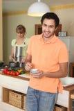 Pares jovenes en una cocina imagen de archivo libre de regalías