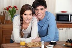 Pares jovenes en una cocina Foto de archivo libre de regalías