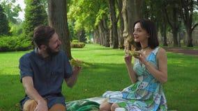 Pares jovenes en una comida campestre en el parque que sostiene el bocadillo almacen de video