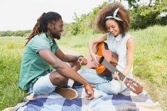 Pares jovenes en una comida campestre que toca la guitarra Foto de archivo