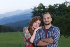 Pares jovenes en una granja Imágenes de archivo libres de regalías