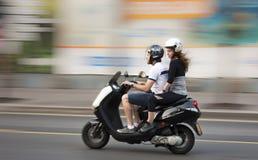 Pares jovenes en una moto Imágenes de archivo libres de regalías