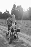 Pares jovenes en una motocicleta en el campo Foto de archivo libre de regalías