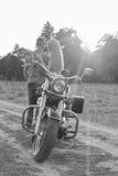Pares jovenes en una motocicleta en el campo Imagen de archivo
