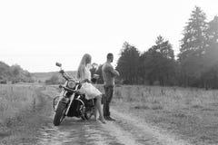 Pares jovenes en una motocicleta en el campo Foto de archivo