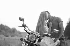 Pares jovenes en una motocicleta en el campo Fotos de archivo libres de regalías