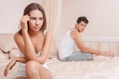 Pares jovenes en una mujer aburrida cama Fotografía de archivo libre de regalías