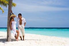 Pares jovenes en una playa Imágenes de archivo libres de regalías