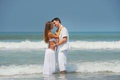 Pares jovenes en una playa Fotos de archivo