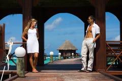 Pares jovenes en una playa tropical Imagen de archivo