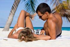Pares jovenes en una playa tropical Foto de archivo libre de regalías