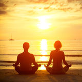 Pares jovenes en una posición de loto meditating en la playa Imagen de archivo