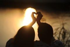 Pares jovenes en una puesta del sol Imágenes de archivo libres de regalías