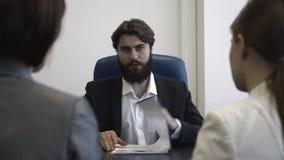 Pares jovenes en una reunión con el agente de la propiedad inmobiliaria Primer almacen de metraje de vídeo
