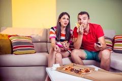 Pares jovenes enrrollados que comen la pizza en un sofá Imagenes de archivo