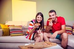 Pares jovenes enrrollados que comen la pizza en un sofá Fotos de archivo
