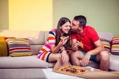 Pares jovenes enrrollados que comen la pizza en un sofá Fotos de archivo libres de regalías