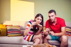 Pares jovenes enrrollados que comen la pizza en un sofá Imágenes de archivo libres de regalías