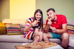 Pares jovenes enrrollados que comen la pizza en un sofá Fotografía de archivo