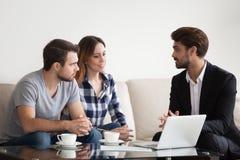 Pares jovenes, familia en el encuentro con del agente inmobiliario, interiorista imagen de archivo