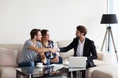 Pares jovenes, familia que hace trato con el agente inmobiliario, interiorista fotografía de archivo