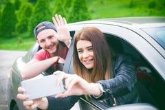 Pares jovenes felices, amigos que hacen el selfie mientras que se sienta en coche Adultos jovenes Gente caucásica Concepto de tra Foto de archivo