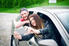 Pares jovenes felices, amigos que hacen el selfie mientras que se sienta en coche Adultos jovenes Gente caucásica Concepto de tra Imágenes de archivo libres de regalías