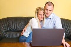 Pares jovenes felices atractivos con la computadora portátil. Fotografía de archivo
