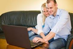 Pares jovenes felices atractivos con la computadora portátil. Fotos de archivo