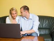 Pares jovenes felices atractivos usando la computadora portátil. Fotografía de archivo