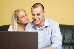 Pares jovenes felices atractivos usando la computadora portátil. Fotos de archivo