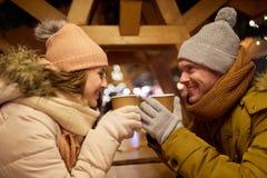 Pares jovenes felices con café en el mercado de la Navidad Foto de archivo