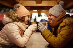 Pares jovenes felices con café en el mercado de la Navidad Fotografía de archivo