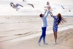 Pares jovenes felices con el bebé que se coloca en agua Foto de archivo libre de regalías