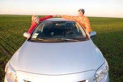 Pares jovenes felices con el nuevo coche imagen de archivo libre de regalías