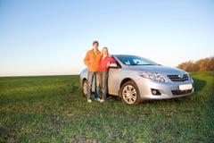 Pares jovenes felices con el nuevo coche Foto de archivo libre de regalías