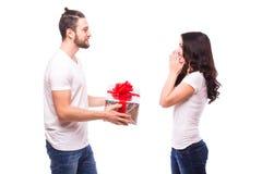 Pares jovenes felices con el presente del día de tarjeta del día de San Valentín aislado en un fondo blanco Imagenes de archivo